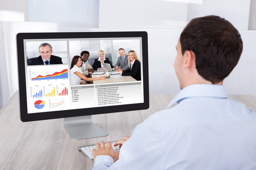 Rear view of businessman video conferencing with colleagues on desktop PC at office desk